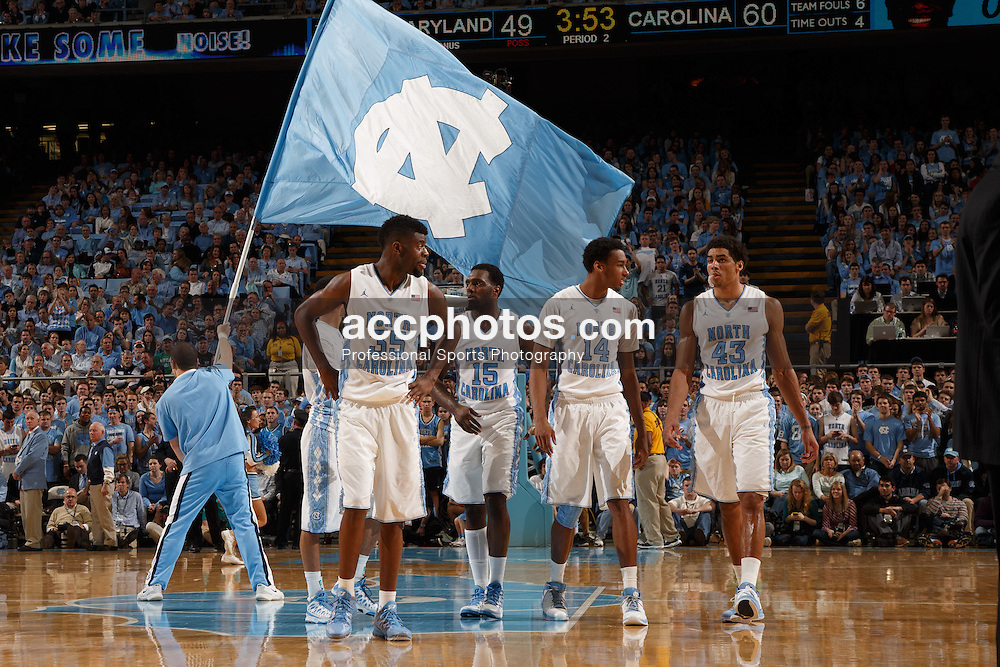 CHAPEL HILL, NC - JANUARY 19: Reggie Bullock #35, P.J. Hairston #15, Desmond Hubert #14 and James Michael McAdoo #43 of the North Carolina Tar Heels walk up the court while a cheerleader holds a flag with the North Carolina logo during a game against the Maryland Terrapins on January 19, 2013 at the Dean E. Smith Center in Chapel Hill, North Carolina. North Carolina won 52-62. (Photo by Peyton Williams/UNC/Getty Images) *** Local Caption *** Reggie Bullock;P.J. Hairston;Desmond Hubert;James Michael McAdoo