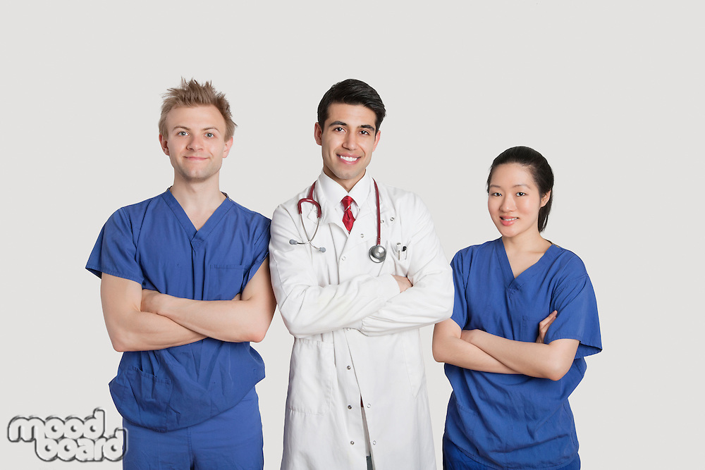Portrait of multi ethnic healthcare professionals standing with arms crossed over gray background