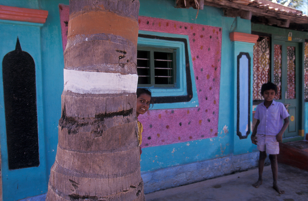 "A brother and sister play ""hide and seek"" outside their colourful home near Mysore, Karnataka, India"