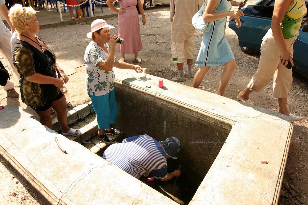 Georgien/Abchasien, Nowy Afon, 2006-08-27, Russische Touristinnen trinken an einer Quelle in Nowy Afon Wasser. Abchasien erklärte sich 1992 unabhängig von Georgien. Nach einem einjährigen blutigen Krieg zwischen den Abchasen und Georgiern besteht seit 1994 ein brüchiger Waffenstillstand, der von einer UNO-Beobachtermission unter personeller Beteiligung Deutschlands überwacht wird. Trotzdem gibt es, vor allem im Kodorital immer wieder bewaffnete Auseinandersetzungen zwischen den Armee der Länder sowie irregulären Kämpfern.  (Russion tourists drinking water at a spring in Nowy Afon. Abkhazia declared itself independent from Georgia in 1992. After a bloody civil war a UNO mission observing the ceasefire line between Georgia and Abkhazia since 1994. Nevertheless nearly every day armed incidents take place in the Kodori gorge between the both armys and unregular fighters )