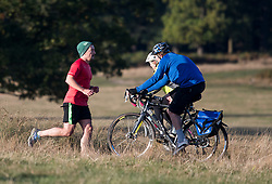 © Licensed to London News Pictures. 27/10/2018. London, UK. A jogger and two cyclists enjoy the bright and sunny conditions in Richmond Park, west London as a cold front hits the capital. snow is expected on high ground in northern parts of the UK over the weekend. Photo credit: Ben Cawthra/LNP