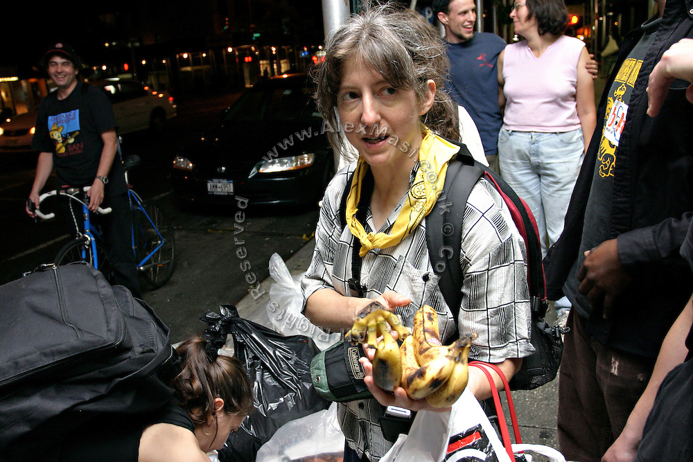 Janet, 43, one of the founders of the Freegan community in New York, holding some bananas found in the rubbish during a trash tour along groceries on 3rd Avenue in Manhattan, New York, NY., on Wednesday, June 21, 2006. Freegans are a community of people who aims at recovering wasted food, books, clothing, office supplies and other items from the refuse of retail stores, frequently discarded in brand new condition. They recover goods not for profit, but to serve their own immediate needs and to share freely with others. According to a study by a USDA-commissioned study by Dr. Timothy Jones at the University of Arizona, half of all food in the United States is wasted at a cost of $100 billion dollars every year. Yet 4.4 million people in the United States alone are classified by the USDA as hungry. Global estimates place the annual rate of starvation deaths at well over 8 million. The massive waste generated in the process fills landfills and consumes land as new landfills are built. This waste stream also pollutes the environment, damages public health as landfills chemicals leak into the ground, and incinerators spew heavy metals back into the atmosphere. Freegans practice strategies for everyday living based on sharing resources, minimizing the detrimental impact of our consumption, and reducing and recovering waste and independence from the profit-driven economy. They are dismayed by the social and ecological costs of an economic model where only profit is valued, at the expense of the environment. In a society that worships competition and self-interest, Freegans advocate living ethical, free, and happy lives centred around community and the notion that a healthy society must function on interdependence. Freegans also believe that people have a right and responsibility to take back control of their time.