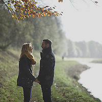 Young adult couple holding hands on the banks of a canal