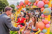 Henham Park, Suffolk, 20 July 2019. A magician does some tricks for three girls in the Next Lounge - A sunny morning with little sign of the showers to come. The 2019 Latitude Festival.