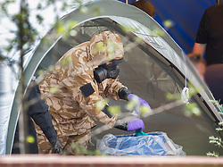 © Licensed to London News Pictures. 06/07/2018. Amesbury, UK. A police officer in a protective suit and gas mask decontaminates after gathering evidence inside a house in Muggleton Road, Amesbury where a couple, named locally as Dawn Sturgess, 44, and her partner Charlie Rowley, 45, were taken ill on Saturday 30th June 2018. Police have confirmed that the couple have been in contact with Novichok nerve agent. Former Russian spy Sergei Skripal and his daughter Yulia were poisoned with Novichok nerve agent in nearby Salisbury in March 2018. Photo credit: Peter Macdiarmid/LNP