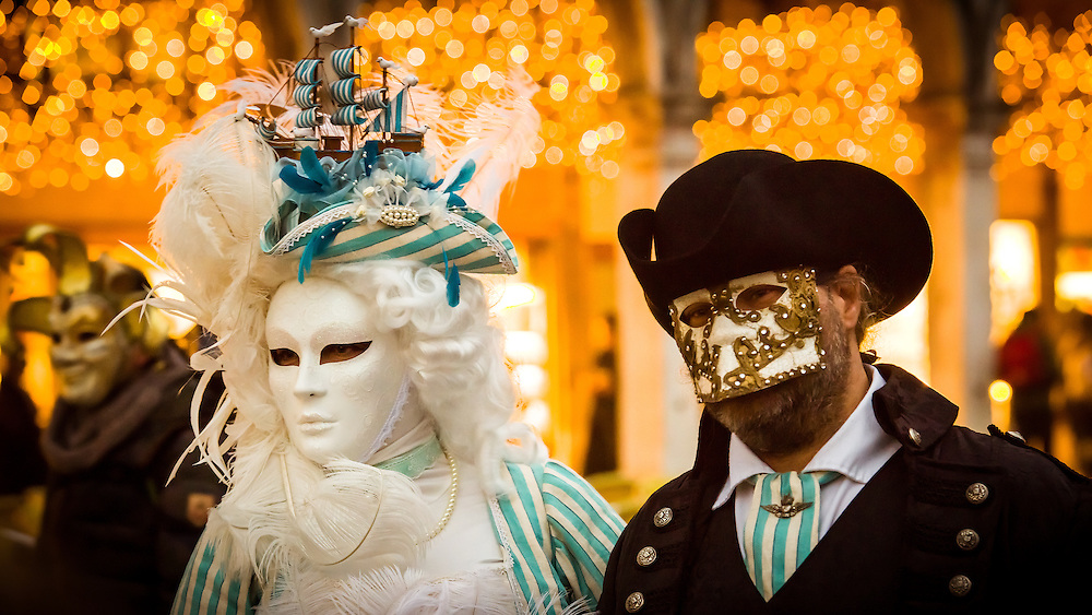 A man and a woman are seen walking through Saint Mark's square in the early evening. They are wearing traditional Volto and Bauta masks