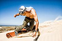 Young man sandboarding on the dunes of Itapiruba Beach. Imbituba, Santa Catarina, Brazil. / <br /> Homem jovem andando de sandboard nas dunas da Praia de Itapirubá. Imbituba, Santa Catarina, Brasil.