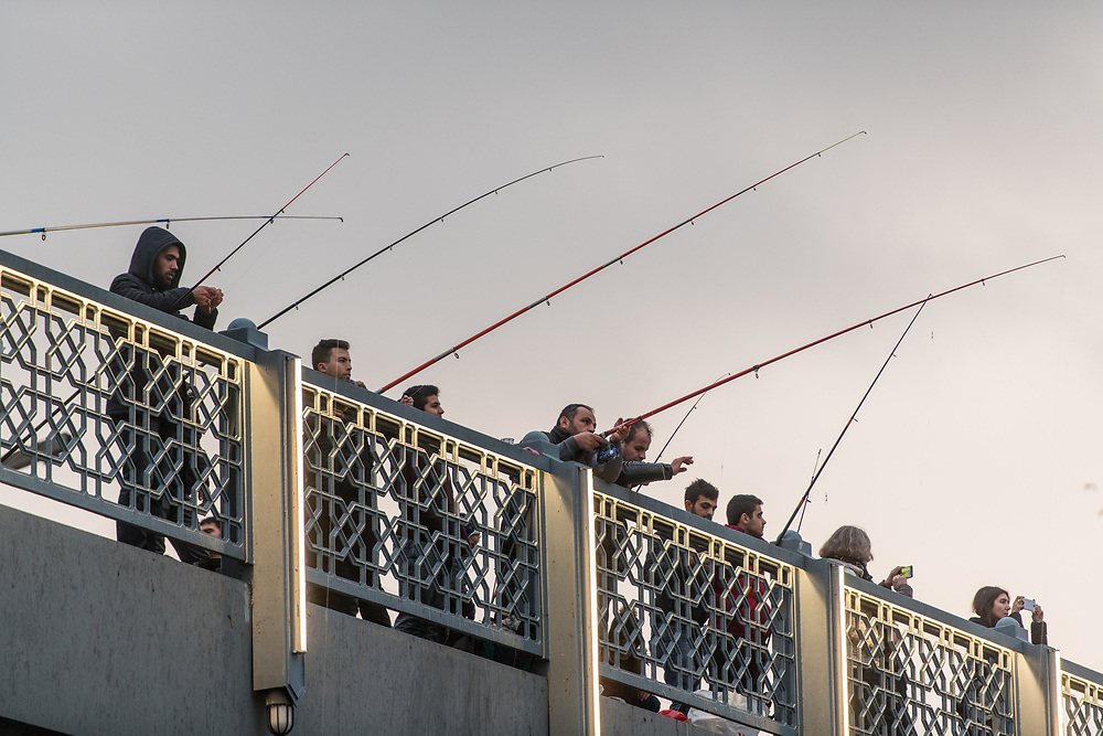 Men cast their fishing lines off of Galata Bridge in hopes of catching a fish, Istanbul, Turkey
