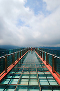 CHONGQING, CHINA - JULY 24: (CHINA OUT) <br /> <br /> World's Longest Glass Skywalk In Huangshui National Forest Park<br /> <br /> Tourists stand on the glass Skywalk at Huangshui National Forest Park on July 24, 2013 in Chongqing, China. The Skywalk, built 300 meters above the bottom of the valley, is a transparent cantilever bridge and tourist attraction. The Skywalk length extending out of the valley wall is 31m, ten meters longer than the Grand Canyon Skywalk. <br /> ©Exclusivepix
