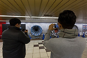 Men take photos of one of three craters in a wall advertising the Jump Force video game for Play Station, X-box and Window PC in Shinjuku Station, Tokyo, Japan. Friday February 22nd 2019. Jump Force  game brings together all the most popular characters from the Shonan Jump manga comics.and was released on February 15th. The punch wall represents the effect of a power punch from characters Son Goku of Dragonball, Naruto and Luffy from One Piece and runs to February 24th