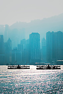South across Hong Kong Harbour. Two Star Ferry passenger boats silhouetted in front of Hong Kong Island city centre buildings