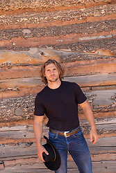 hot cowboy with long brown hair and blue eyes against a rustic wooden barn