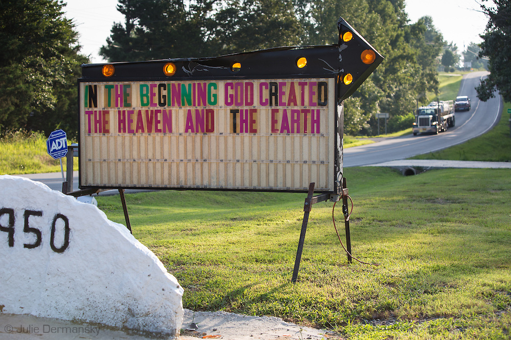 Fracking industry truck drives by a church sign in Quitman Arkansas.