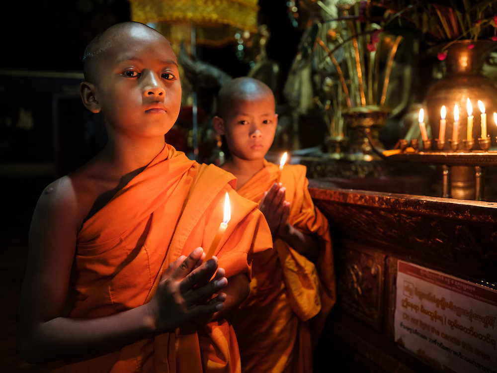 KYAING TONG, MYANMAR - CIRCA DECEMBER 2017: Monks at the Wat Jong Kham Monastery with candles looking at camera.