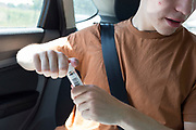 A young man in his twenties pushes a swab up his nose while sitting in the rear seat of a car during a self-administered Coronavirus (COVID-19) test in south London. There are four steps to the self-administered Covid-19 test (inserting a swab into the nose and throat) which the public works through in their car, windows up and all communications with army personnel via phone, in a south London leisure centre, on 2nd June 2020, in London, England. The kit provided consists of a booklet, plastic bag, swab, vial, bar codes and a sealable biohazard bag. The swab sample is taken from the back of the throat and nasal passage with the contents sealed and returned to soldiers through a narrow window. The whole process takes between 5-10mins with results available with 48hrs.