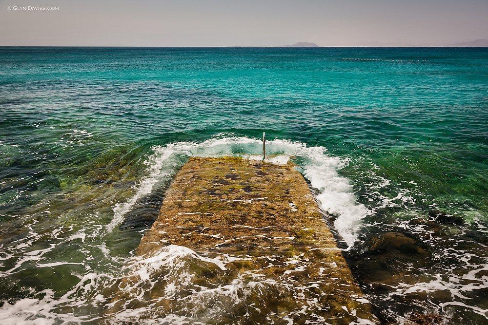 An ocean swell only shows it's energy as it reaches the shoreline and wraps around a swimming platform on the shore of Playa Blanca in Lanzarote in the Canary Islands. The aquamarine sea is crystal clear and you can see the reef beneath. Lobos Island and Fuerteventura can be see on on the horizon.
