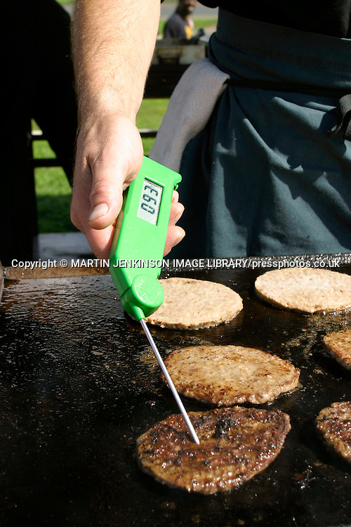 Checking the internal temperature of a beefburger with a digital thermometer.