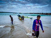 03 AUGUST 2017 - KUTA, BALI, INDONESIA: Men walkaway from an outrigger canoe on Jimbrana Beach in Kuta. The beach is close to the airport and a short drive from other beaches in southeast Bali. Jimbrana was originally a fishing village with a busy local market. About 25 years ago, developers started building restaurants and hotels along the beach and land prices are rising. The new emphasis on tourism is changing the nature of the area but the fishermen are still busy very early in the morning.     PHOTO BY JACK KURTZ