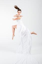Female Dancer Leaping Mid Air in White Long Dress