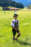 Young boy in costume strolls through flower meadow during traditional beer festival in the village of Klais in Bavaria, Germany