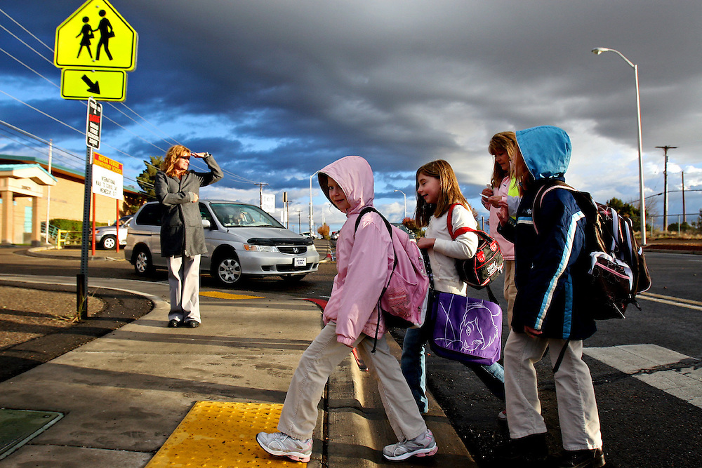 Xavier Mascareñas/The Daily Times; Cynthia Sosaya, the new principal at Mesa Verde Elementary, keeps an eye out for her students crossing College Boulevard in Farmington, N.M., with the help of a crossing guard during International Walk to School Day on Oct. 7, 2009.