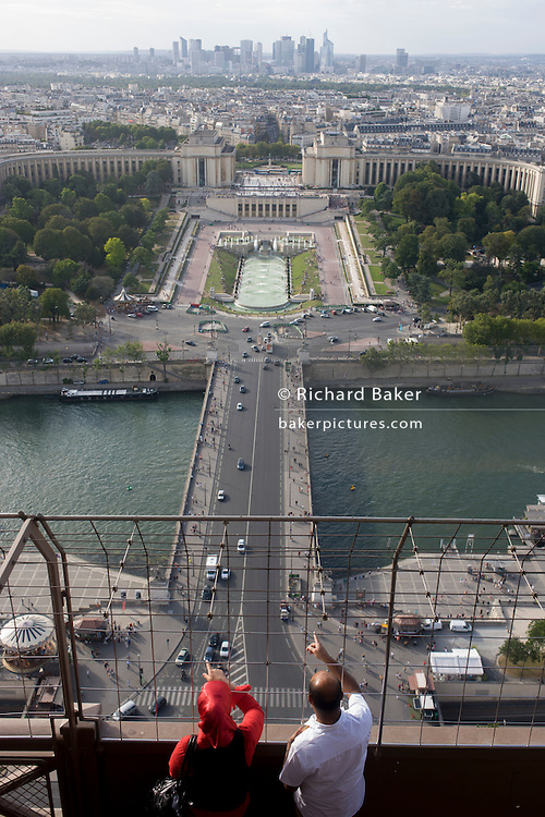 Tourists point out landmarks from the second level of the Eiffel Tower, Paris.