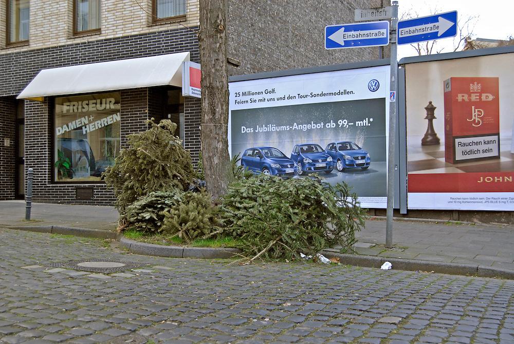 DEU,Deutschland,Koeln,Nordrhein-Westfalen,Ein Haufen weggeworfener Weihnachtsbäume liegt auf der Strasse vor einem Frisörladen und einem Werbeplakat für den VW Golf      |  Christmas trees on the street in front of a barber shop and an advertising wall for the VW Golf after sale of the 25th million model  |