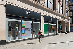 © Licensed to London News Pictures. 20/07/2020. London, UK. A woman walks past the Marks and Spencers flagship store in Oxford St. The company is reported to announce this week job losses and more store closures due to the Covid-19 lockdown and prior poor sales. Photo credit: Ray Tang/LNP