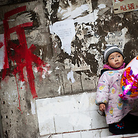 """2 years old plays with a colorful baloon in a sink in a hutong near to Chiaotianmen. He and his family will have to move next year as his house is part of the modernization of the area. Left on the wall, in red, the """"Chai"""" character, meaning his house is condemned. Chongqing, China - The most populous city in the world"""