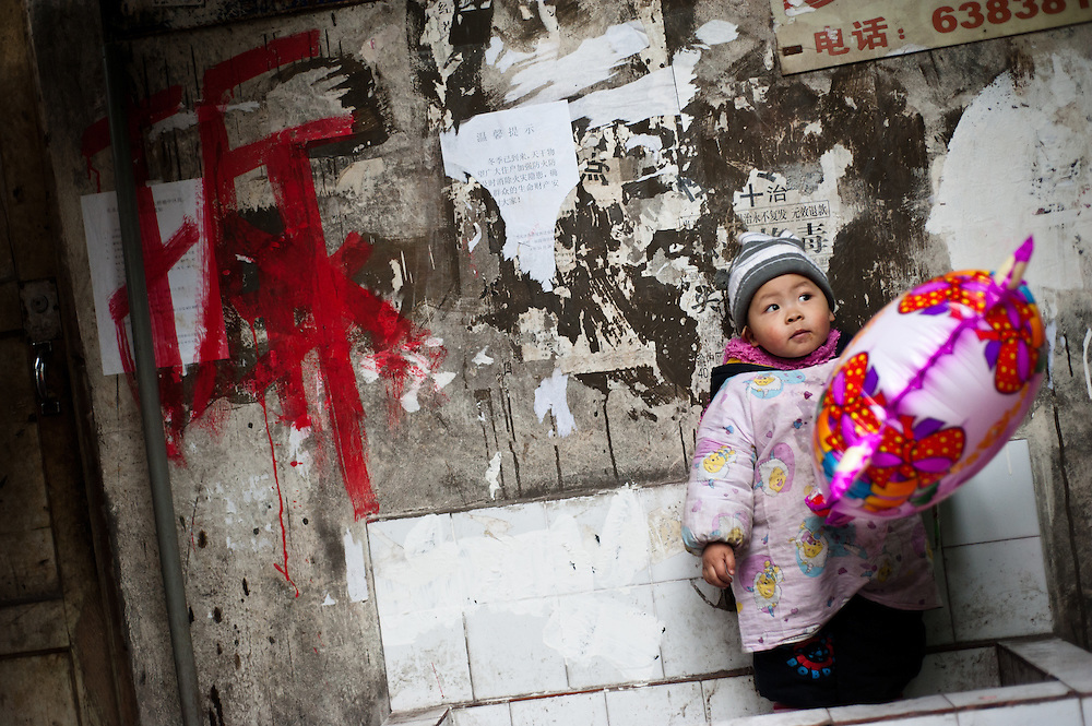 "2 years old plays with a colorful baloon in a sink in a hutong near to Chiaotianmen. He and his family will have to move next year as his house is part of the modernization of the area. Left on the wall, in red, the ""Chai"" character, meaning his house is condemned. Chongqing, China - The most populous city in the world"