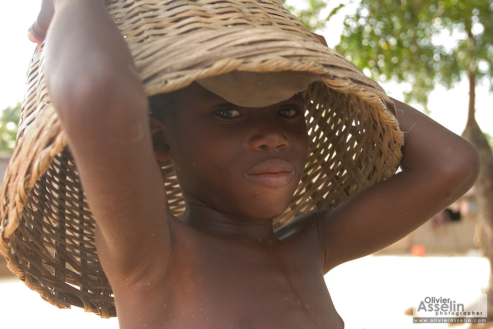 Young Ghanaian boy with a basket on his head.