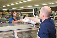 Supermarket employee hands product to customer in supermarket delicatessen