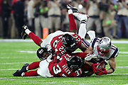 New England Patriots wide receiver Julian Edelman (11) is defended by Atlanta Falcons free safety Ricardo Allen (37), Falcons cornerback Robert Alford (23) and Falcons rookie strong safety Keanu Neal (22) as Edelman makes a diving circus catch with the ball inches off the turf on a pass reception good for a gain of 23 yards and a first down at the Falcons 41 yard line on a key fourth quarter drive with two minutes left in regulation play during the Super Bowl LI football game against the Atlanta Falcons on Sunday, Feb. 5, 2017 in Houston. The Patriots won the game 34-28 in overtime. (©Paul Anthony Spinelli)