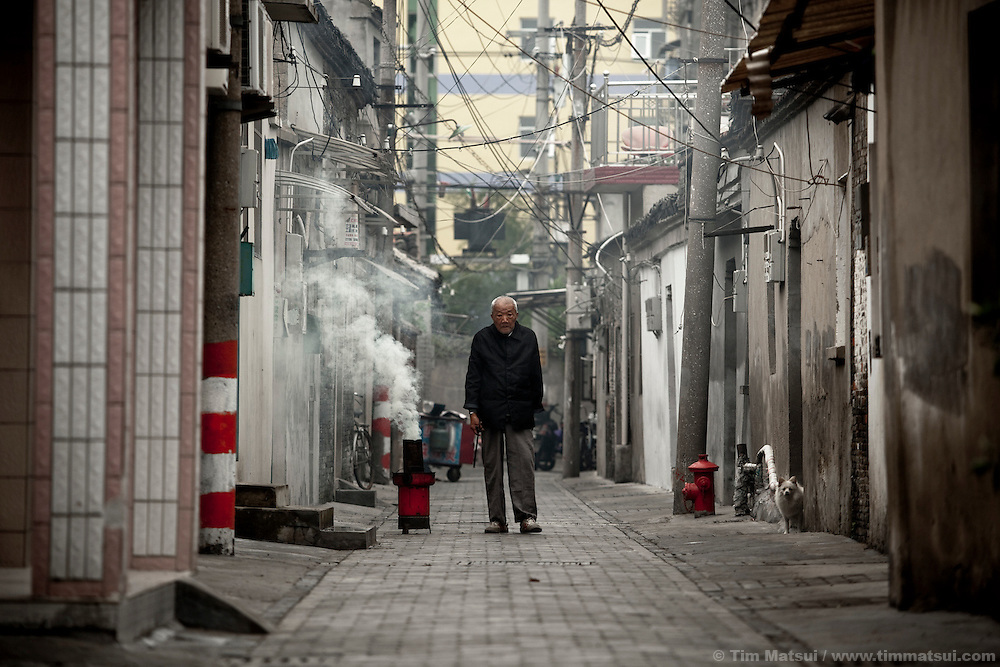 Old man in an alley starts a charcoal fire for cooking, Yangzhou, China, a suburb city of Shanghai and major producer of photovoltaic cells for solar power.