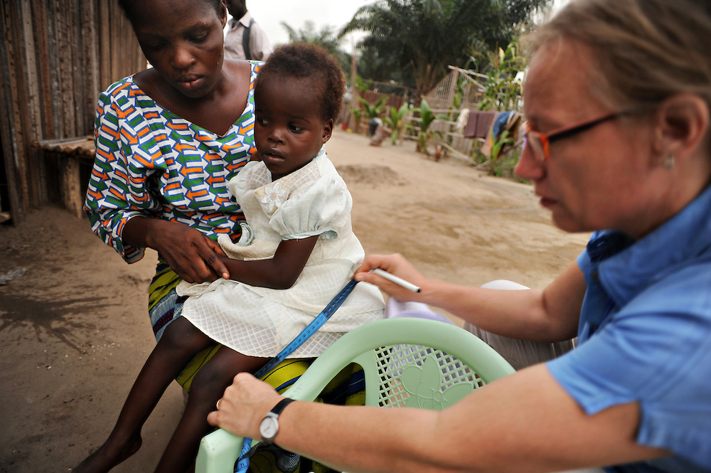 12-02-07  --  AMPAIN, GHANA -- Marjolein Baltussen, coordinator of mother and child health and early childhood development programs with the Presbyterian Church of Ghana, measures five-year-old Koussenda Djaone at the Ampain Refugee Camp on February 7. Her mother, Deborah Djaone says her daughter can't walk or crawl and spends her days sitting in a plastic chair, pictured.  Unless therapy is provided, Koussenda's situation will worsen, says Baltussen.    Photo by Daniel Hayduk