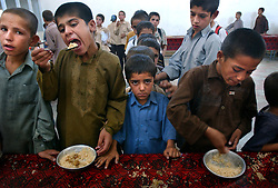 Afghan orphans wait in line to eat lunch at an overcrowded orphanage in Kabul, Afghanistan September 1, 2002. There are not enough bowls or tables so the 1800 children must wait in line for the next child to finish before they can eat. Despite the huge amounts of foreign aid being brought into the country, many schools and orphanges have seen none of it yet and the alarming rates of child mortality continue to remain among the worst in the world. One in four children die before the age of 5 here.