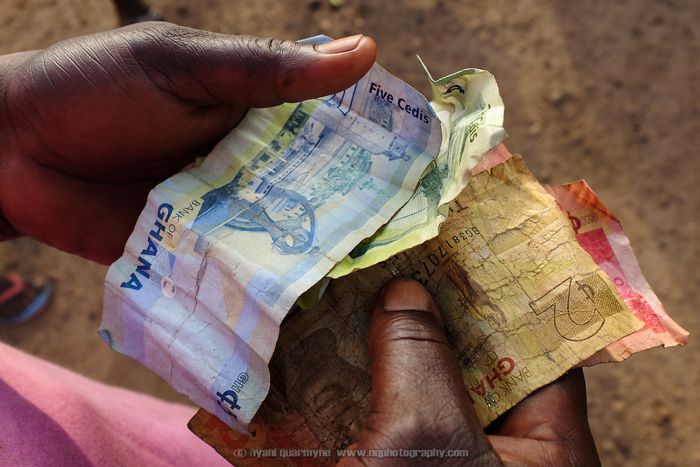 "Cash in a member's hands at a meeting of a women's ""susu"" group - an informal savings and loan club - in the village of Gbengbee in the Upper West region of Ghana. The women's activities are supported by Pognaa Tang I - a pognaa is responsible, in particular, for the wellbeing of women and children in her area of authority. While the title translates as ""woman chief"", in practice her authority is  subject to a male chief. The role of the pognamine (plural of pognaa) is being revived after having been suppressed during the colonial era, and they are increasingly seen as a force for development."