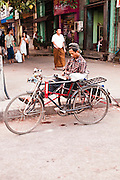 Trishaw driver taking a break to read. Yangon, Myanmar.