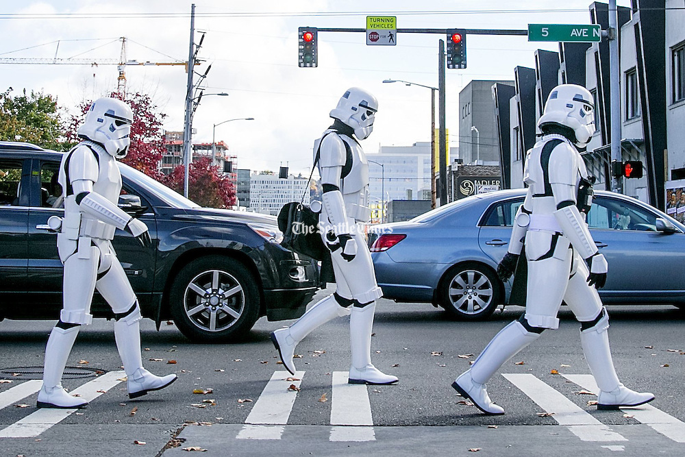 """Dino Ignacio, left, of West Seattle; Guy Evans, of Tacoma; and Casey Buxton, of Vashon Island, cross the street on their way to the EMP Museum in Seattle on Sunday. The friends are members of the 501st Legion, an all-volunteer organization that promotes interest in """"Star Wars"""" while appearing at local community and charity events. They thought it would be fun to check out the EMP Museum's sci-fi exhibit while wearing their storm-trooper outfits. (Johnny Andrews/The Seattle Times)"""