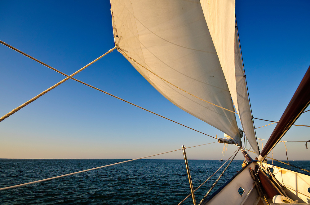 Sailboat navigating towards sunset in the caribbean.