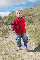 Boy (3-4) walking on sand dunes