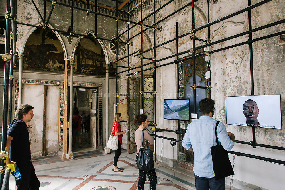 PALERMO, ITALY - 15 JUNE 2018: Visitors watch &quot;The Body's Legacies. The Post-Colonial Body, 2018, 2018&quot; by artist Kader Attia at Palazzo Forcella De Seta during Manifesta 12, the European nomadic art biennal, in Palermo, Italy, on June 15th 2018.<br /> <br /> Manifesta is the European Nomadic Biennial, held in a different host city every two years. It is a major international art event, attracting visitors from all over the world. Manifesta was founded in Amsterdam in the early 1990s as a European biennial of contemporary art striving to enhance artistic and cultural exchanges after the end of Cold War. In the next decade, Manifesta will focus on evolving from an art exhibition into an interdisciplinary platform for social change, introducing holistic urban research and legacy-oriented programming as the core of its model.<br /> Manifesta is still run by its original founder, Dutch historian Hedwig Fijen, and managed by a permanent team of international specialists.<br /> <br /> The City of Palermo was important for Manifesta&rsquo;s selection board for its representation of two important themes that identify contemporary Europe: migration and climate change and how these issues impact our cities.