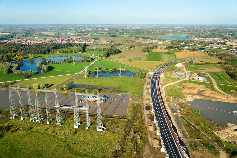 Nederland, Gelderland, Nijmegen, 24-10-2013; grondwerkzaamheden voor de dijkteruglegging Lent (Ruimte voor de Rivier). De dijken worden landinwaarts verplaats en er wordt een nevengeul voor rivier de Waal gegraven. Toerit van de nieuwe stadsbrug van Nijmegen, De Oversteek. Koudenhoek linksboven in beeld.<br /> new city bridge of Nijmegen on the river Waal, De Oversteek (The Crossing). Groundworks for the Dike relocation of Lent (project Ruimte voor de Rivier: Room for the River). <br /> luchtfoto (toeslag op standaard tarieven);<br /> aerial photo (additional fee required);<br /> copyright foto/photo Siebe Swart.