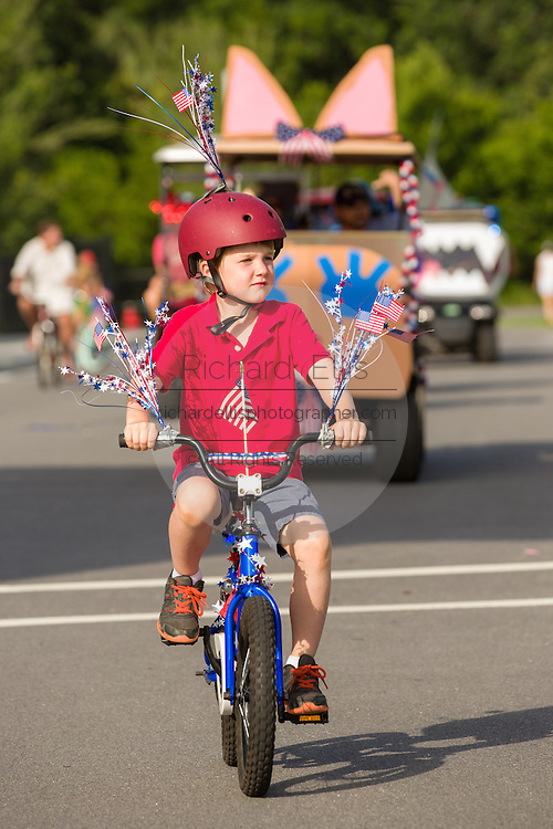 A young boy rides his bicycle decorated with bunting and American flags during the Sullivan's Island Independence Day parade July 4, 2015 in Sullivan's Island, South Carolina.