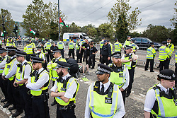 London, UK. 2 September, 2019. Police officers form a cordon around activists locked on using an arm tube to block a road outside ExCel London on the first day of week-long protests against DSEI 2019, the world's largest arms fair. The first day of creative action was hosted by activists calling for a ban on arms exports to Israel and featured workshops, speakers, street theatre and dance. Israeli arms companies display weapons at DSEI marketed as 'combat-proven' following deployment against Palestinian communities.