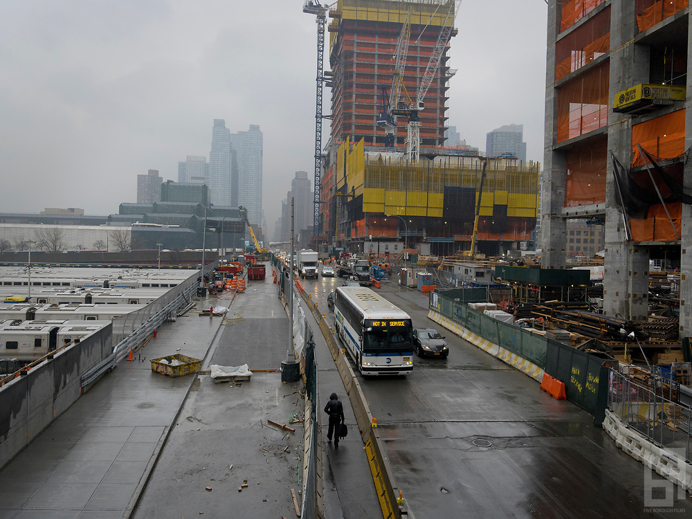 Man walks along Hudson Yards development project in Manhattan as an out of service MTA bus passes him on the street. 50 Hudson Yards can be seen under construction in the background