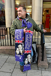 © Licensed to London News Pictures. 12/10/2018. WINDSOR, UK.  A souvenir salesman with scarves as crowds gather in Windsor for the royal wedding of Princess Eugenie and Jack Brooksbank.  Princess Eugenie, 28, the younger daughter of the queen's third child Prince Andrew and his ex-wife Sarah Ferguson, the Duchess of York, will marry Jack Brooksbank, a 32-year-old drinks executive, in Windsor Castle before taking part in a short carriage procession through Windsor town.  This is the second royal wedding in Windsor in 2018, Prince Harry married Meghan Markle in May.  Photo credit: Stephen Chung/LNP