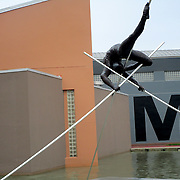 The letter M being shoot through a sculpture of a man holding sticks in the air, while another happens to walk through. (Photo by Norzilia Mezinord).
