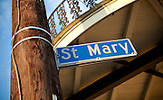 St. Mary street sign attached to wooden electrical pole with wrought iron balcony above