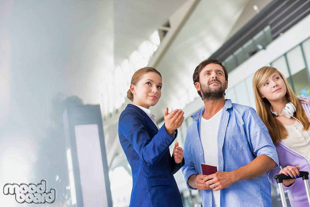 Mature man traveling with her sister while asking for assistance with the airport staff